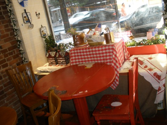 Interior of Two Little Red Hens: cute red tables, all-American checkered and cherry tablecloths, American flags, suburban mommy's kitchen tools hanging on the walls, etc.