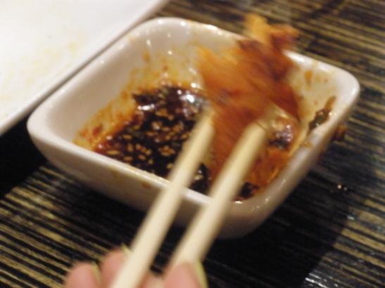 Dipping kimchi jun into sauce.
